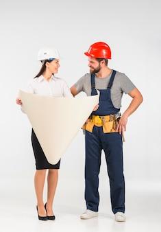 Mulher engenheiro e construtor discutindo projeto sorrindo
