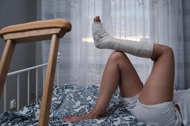 Mulher engessada deitada na cama em casa, muletas por perto.