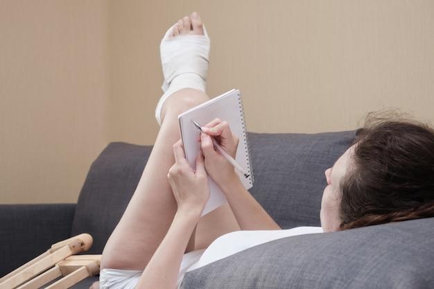 Mulher engessada escrevendo no caderno, deitada em um sofá na sala de estar de casa