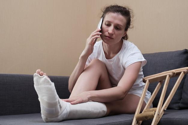 Mulher engessada, falando ao telefone, sentada no sofá da sala de estar em casa.