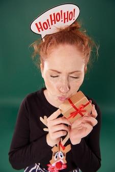 Mulher engraçada abraçando um presente de natal