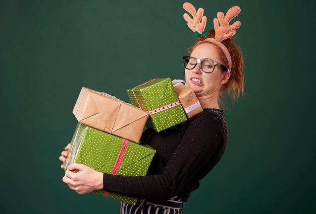 Mulher engraçada carregando uma pilha de presentes de natal
