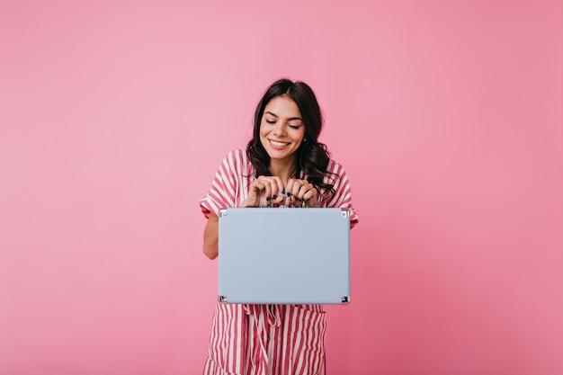 Mulher engraçada com cabelo escuro encaracolado ri após uma brincadeira de sucesso e tem uma maleta retrô nas mãos.