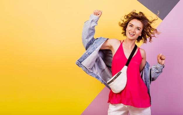 Mulher engraçada com cabelos ondulados curtos, dançando e se divertindo em multicolor.