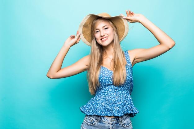Mulher engraçada com chapéu de palha, mostrando a língua em pé perto de uma parede azul, diversão, estilo de vida, interior