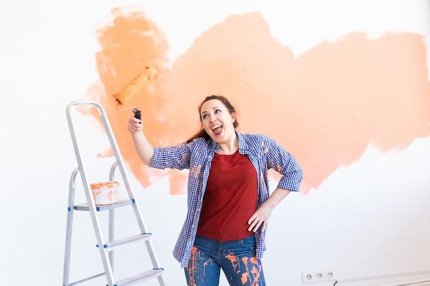 Mulher engraçada dançando pintando as paredes da nova casa. conceito de renovação, reparação e redecoração.