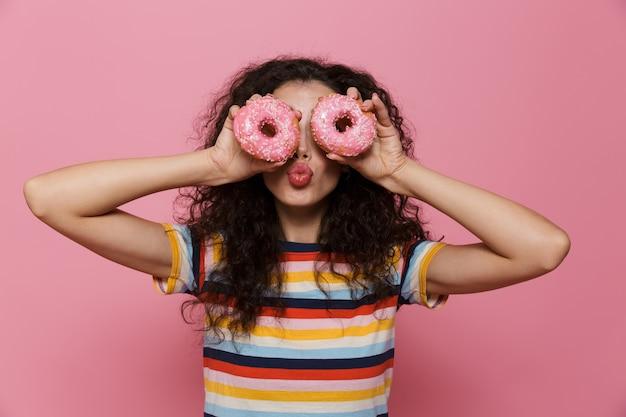 Mulher engraçada de 20 anos com cabelo encaracolado brincando e segurando rosquinhas isoladas no rosa