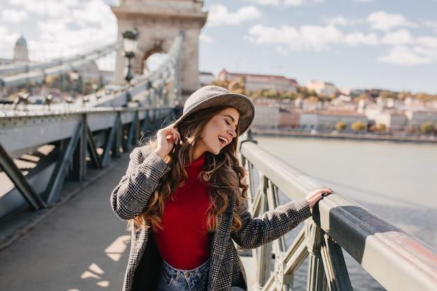 Mulher engraçada de cabelo comprido com chapéu posando com os olhos fechados durante a sessão de fotos na ponte em um dia ensolarado