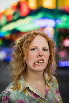 Mulher engraçada de cara boba no parque de diversões