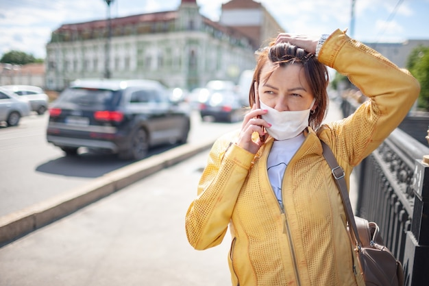 Mulher engraçada de meia-idade com uma máscara protetora branca falando em um smartphone enquanto caminhava pela cidade em um dia quente de primavera