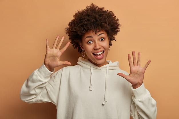 Mulher engraçada de pele escura étnica tem cabelo encaracolado, se move com alegria, mantém as palmas das mãos voltadas para a câmera e usa um moletom branco casual
