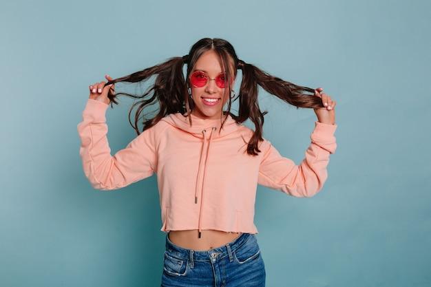 Mulher engraçada e atraente com cabelos presos, vestindo uma blusa rosa brincando com o cabelo dela, usando roupas casuais posando sobre uma parede azul