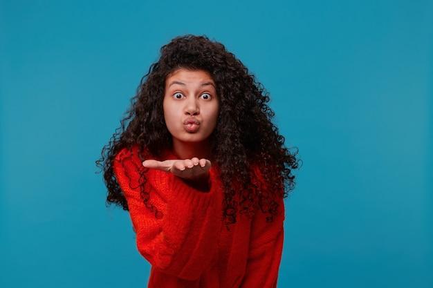 Mulher engraçada em suéter vermelho com adorável cabelo preto encaracolado olhando para a frente e mandando um beijo no ar