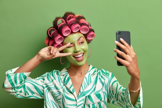 Mulher engraçada feliz faz selfie formas sinal de vitória na câmera do smartphone sorri amplamente aprecia tratamentos faciais; aplique rolos de cabelo vestidos com roupas casuais domésticas, isolados sobre a parede verde