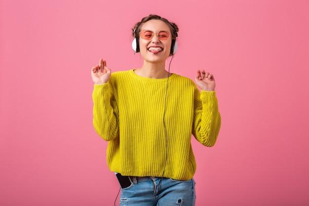 Mulher engraçada feliz ouvindo música em fones de ouvido, vestida com roupa de estilo moderno colorido, isolada na parede rosa, vestindo suéter amarelo e óculos escuros, se divertindo mostrando a língua