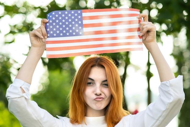 Mulher engraçada jovem feliz posando com a bandeira nacional dos eua, segurando-o nas mãos estendidas em pé ao ar livre no parque de verão. menina positiva comemorando o dia da independência dos estados unidos.