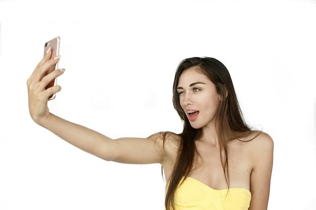 Mulher engraçada leva selfie em seu telefone em pé no fundo branco
