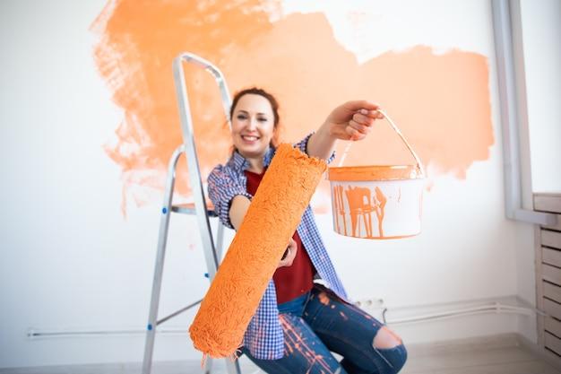 Mulher engraçada pintando a parede interna da casa com rolo de pintura