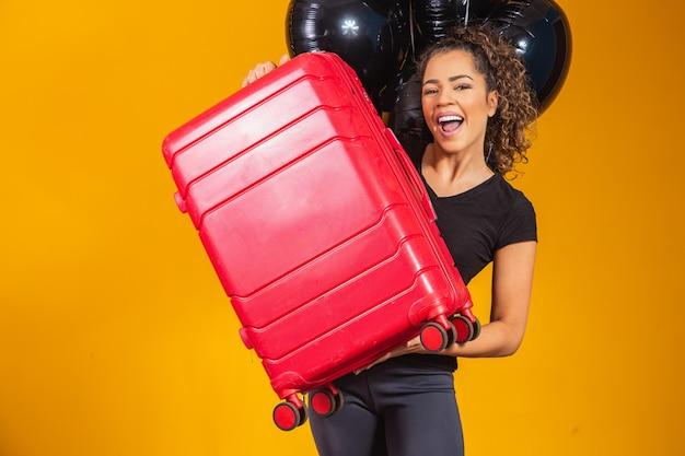 Mulher engraçada segurando uma bolsa de viagem pesada. aniversário de promoção de viagem. black friday em passagens aéreas.