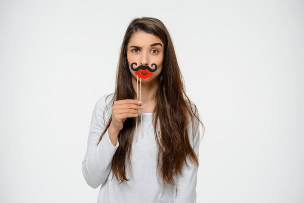 Mulher engraçada segure bigode falso e lábios, festejando