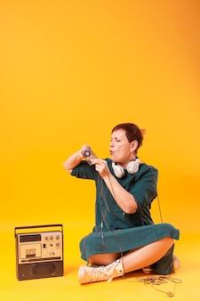Mulher engraçada sênior coberta com fita cassete