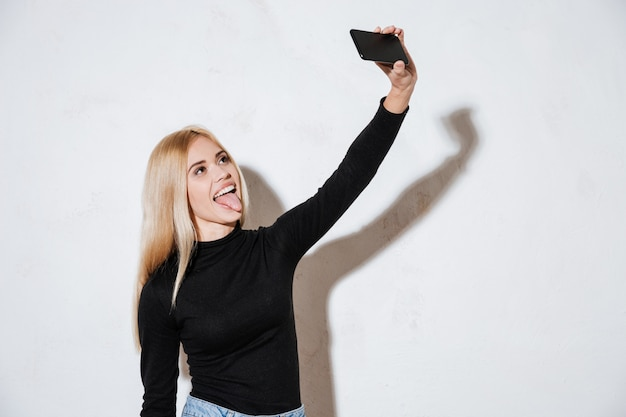 Mulher engraçada sorridente, mostrando a língua enquanto estiver a tomar selfie