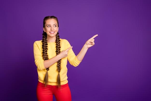 Mulher engraçada tranças compridas com penteado indicando espaço vazio com dedo, vestir pulôver amarelo casual calça vermelha isolada na parede roxa