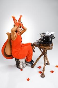 Mulher engraçada, vestida como um esquilo, digitando com a velha máquina de escrever