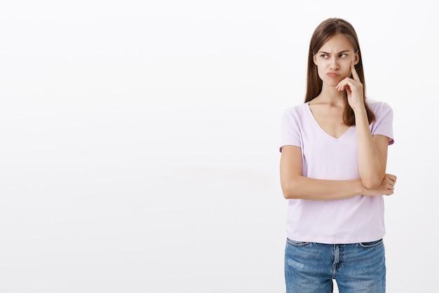 Mulher enjoada incomodada, inveja, colega de trabalho, flertando com o cara bonito do escritório, franzindo a testa, sentindo-se irritada e chateada, franzindo os lábios, olhando para a esquerda com desdém e desprezo, segurando o dedo na bochecha, xingando