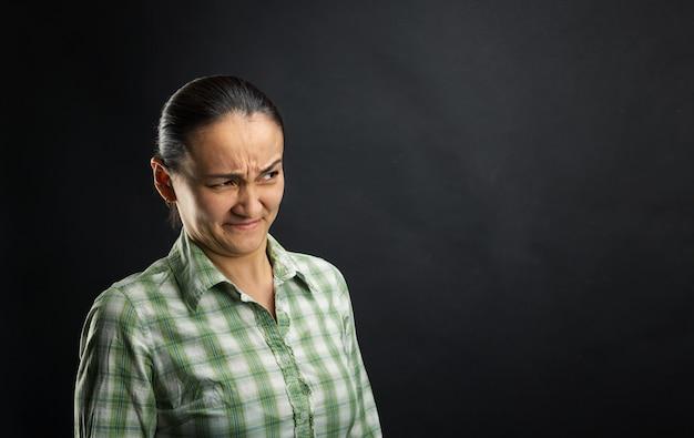 Mulher enojada em pé sobre um fundo preto