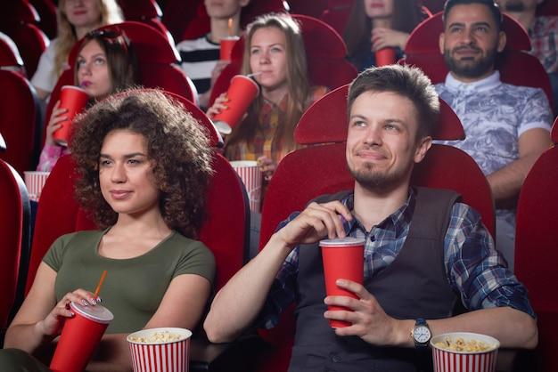 Mulher enrolada e homem com barba no cinema.
