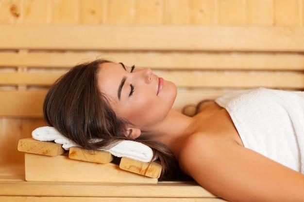 Mulher enrolada em toalha branca deitada na sauna