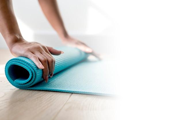 Mulher enrolando um tapete de ioga durante quarentena de coronavírus