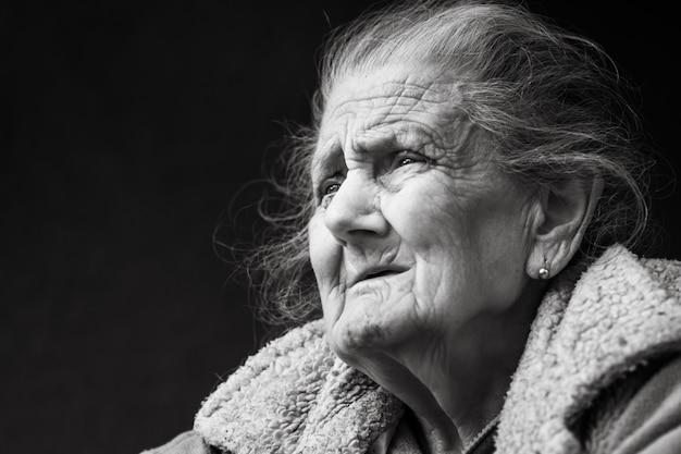 Mulher enrugada muito velha e cansada ao ar livre