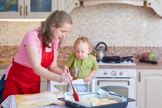 Mulher ensina uma criança a cozinhar bolos. unte as tortas na assadeira com uma escova de cozinha.