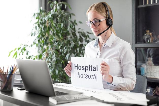 Mulher ensinando a seus alunos a definição de hospital