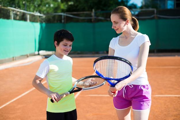 Mulher, ensinando, criança, como, segurar, um, raquete tênis