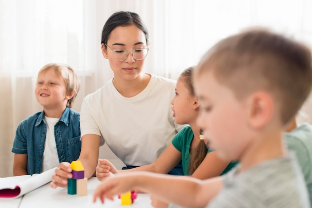 Mulher ensinando crianças a brincar com um jogo colorido
