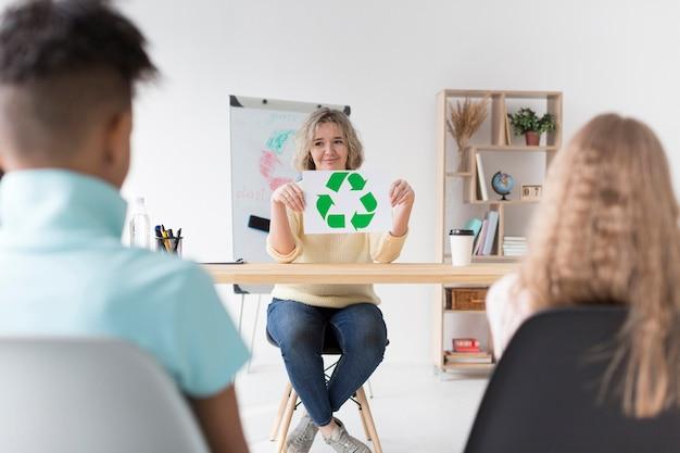Mulher ensinando crianças a reciclar