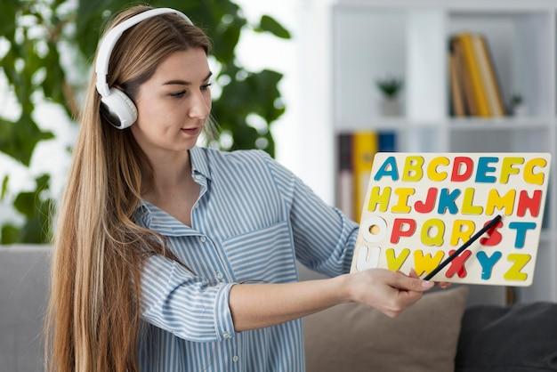 Mulher ensinando crianças na aula de inglês online