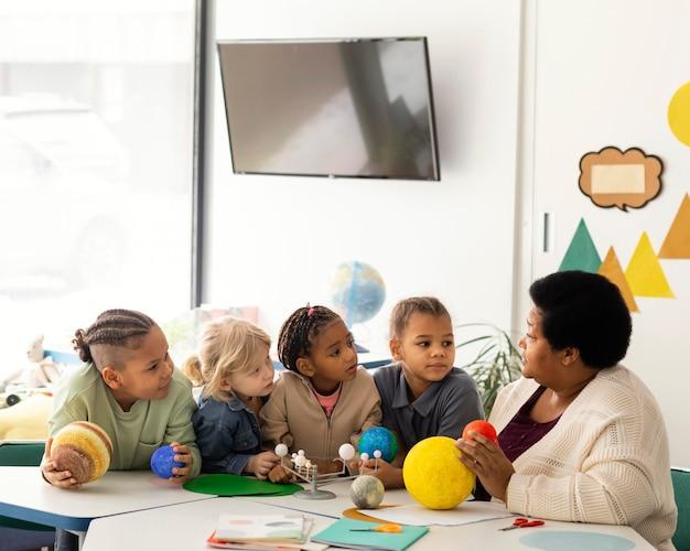 Mulher ensinando crianças sobre planetas