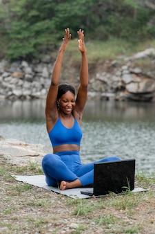Mulher ensinando ioga para pessoas online