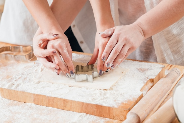 Mulher ensinando outra a trabalhar com massa e a usar o cortador