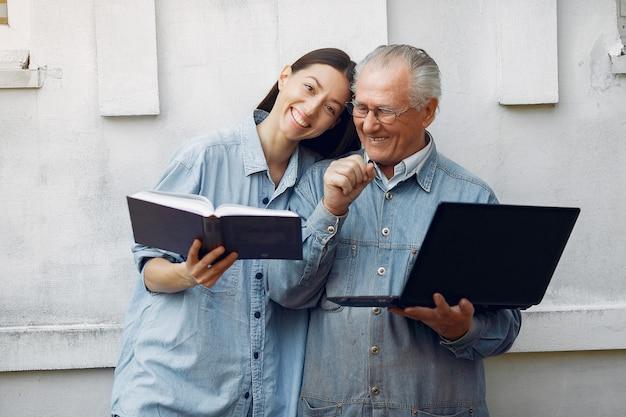 Mulher ensinando seu avô como usar um laptop