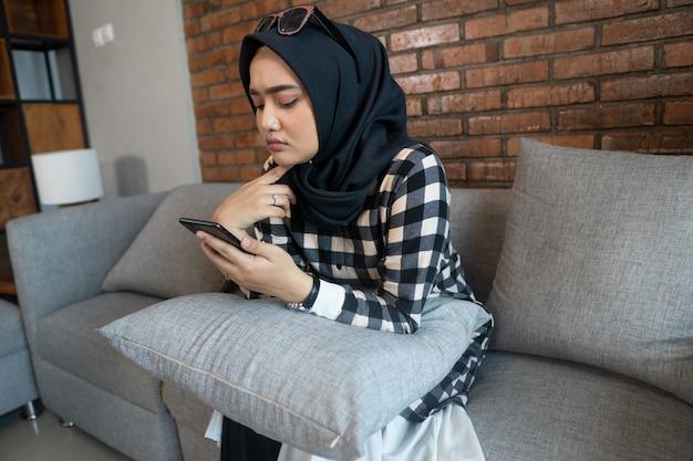 Mulher entediada em casa usando seu telefone celular