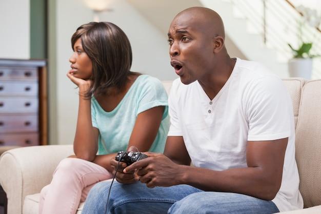 Mulher entediada sentada ao lado de seu namorado jogando videogames