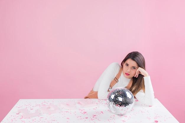 Mulher entediada sentado à mesa com bola de discoteca