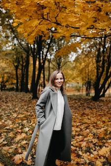 Mulher entra ao longo do beco de outono do parque uma garota com um casaco cinza