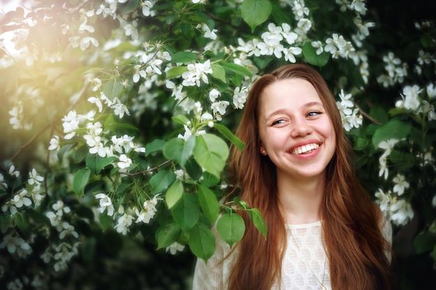 Mulher entre as flores da primavera na natureza
