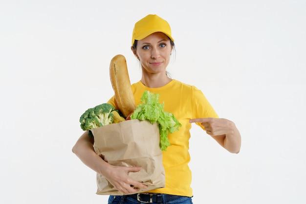 Mulher entrega apontando para sacola de compras na mão